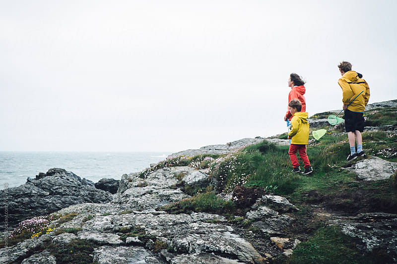 three kids standing ont he rocks but the sea by Léa Jones for Stocksy United
