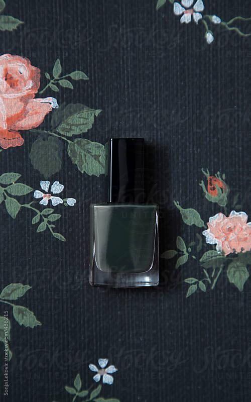 dark green nail polish on black decorative background by Sonja Lekovic for Stocksy United