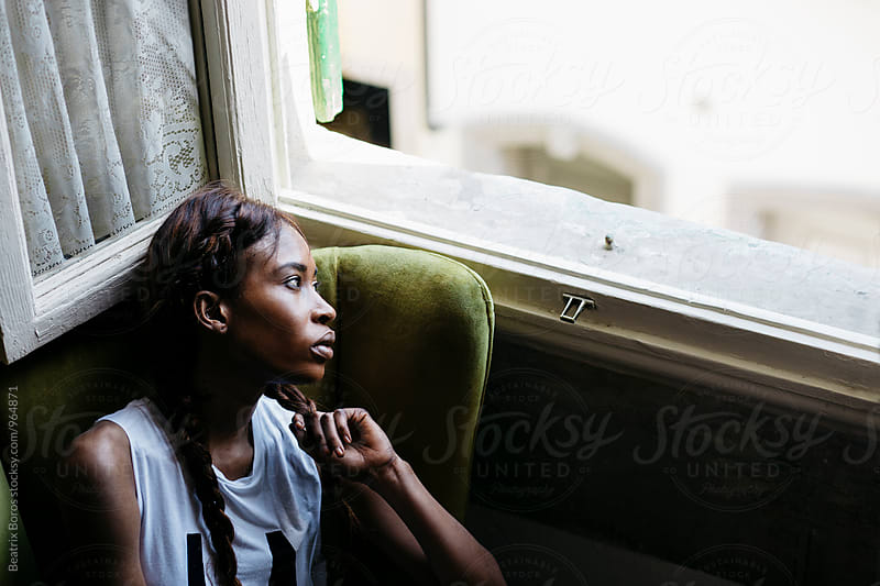 Young black woman in an armchair looking out of the window by Beatrix Boros for Stocksy United