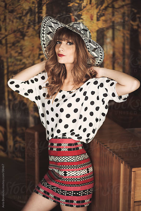 A beautiful woman in a polka dot blouse posing for the camera by Ania Boniecka for Stocksy United