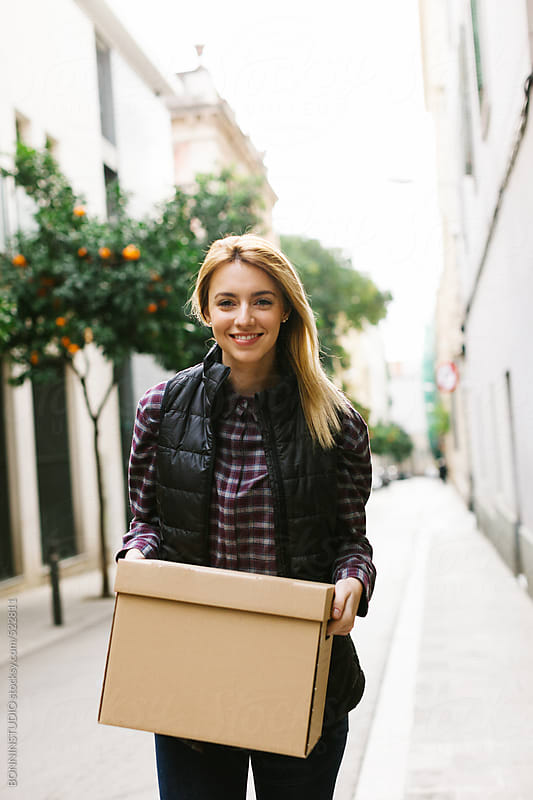 Young woman carrying a box for moving into a new home.  by BONNINSTUDIO for Stocksy United