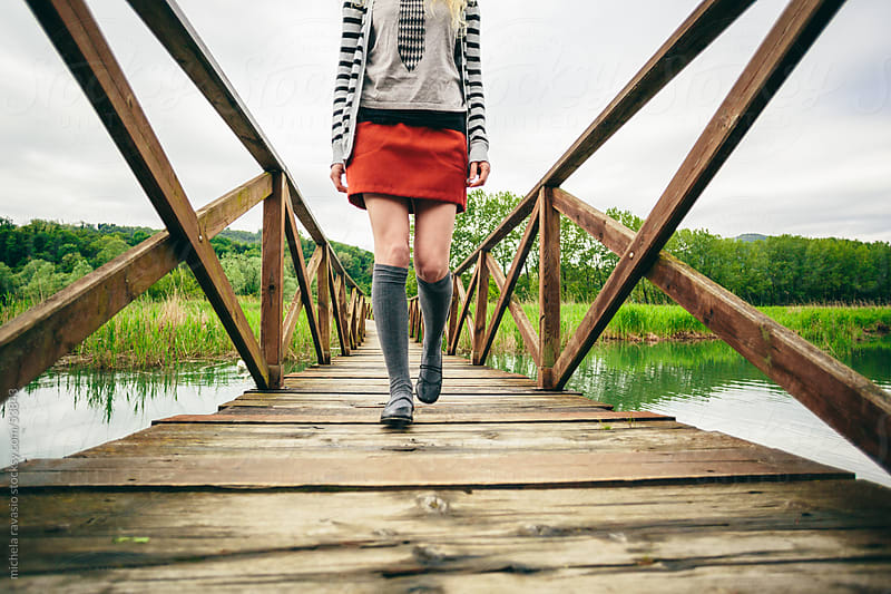 Young woman walking on a pier by michela ravasio for Stocksy United