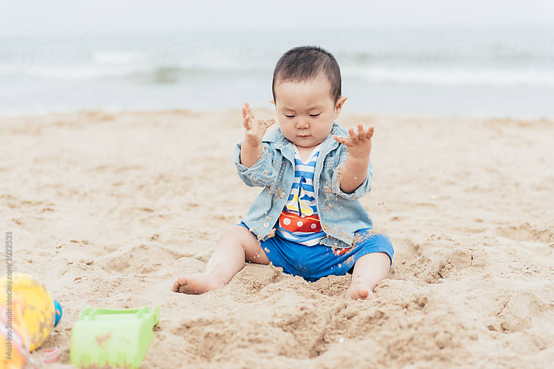 Cute baby playing in sand by Maa Hoo for Stocksy United