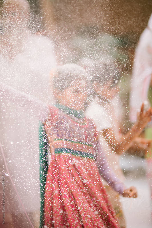 Young girl celebration with snow spray and confetti by Murtaza Daud for Stocksy United