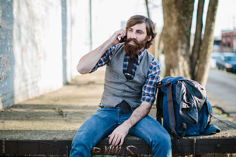 A hipster with a beard sitting down while talking on the phone by Jakob for Stocksy United