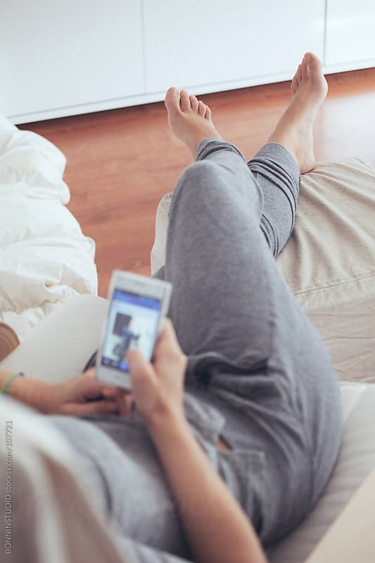 Woman relaxing with smart phone at home. by BONNINSTUDIO for Stocksy United