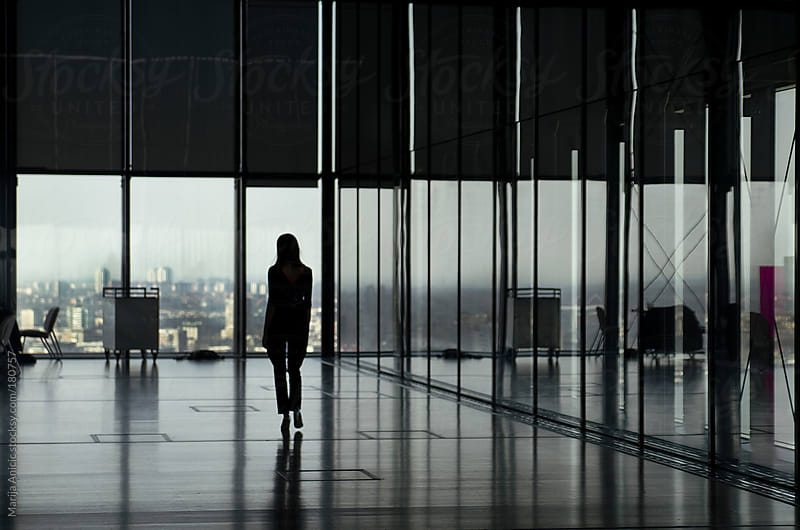 Silhouette of woman in big space with big windows and city view by Marija Anicic for Stocksy United
