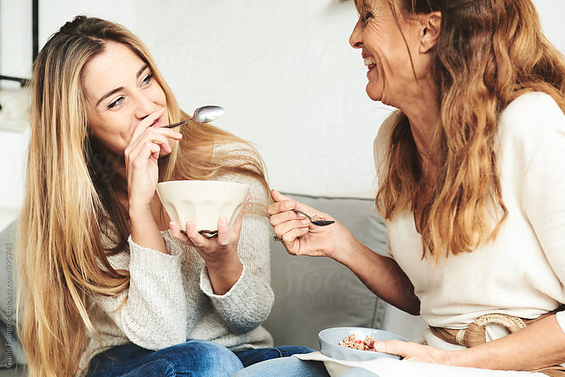 Laughing women sitting on sofa while holding plates with muesli, Mother and daughter by Guille Faingold for Stocksy United