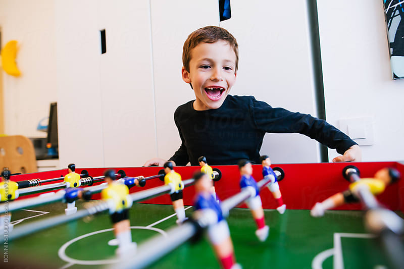 Little boy playing table football at home. by BONNINSTUDIO for Stocksy United