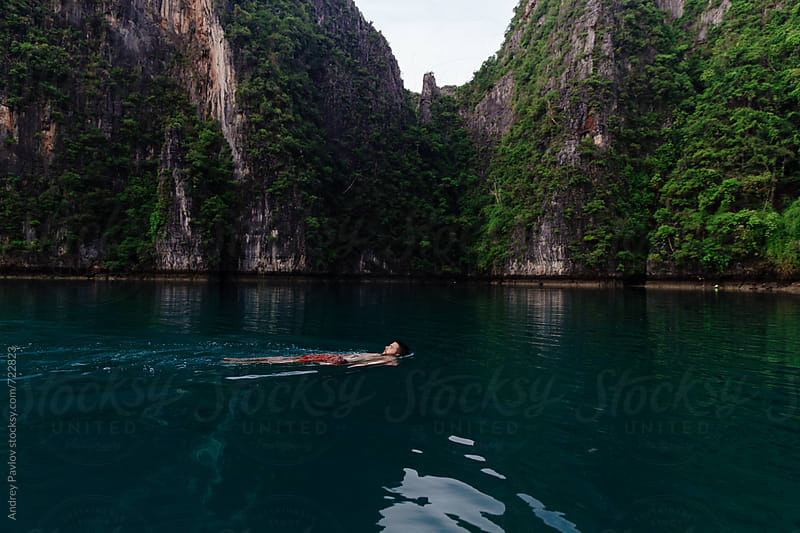 Man swimming in the lagoon on the back by Andrey Pavlov for Stocksy United