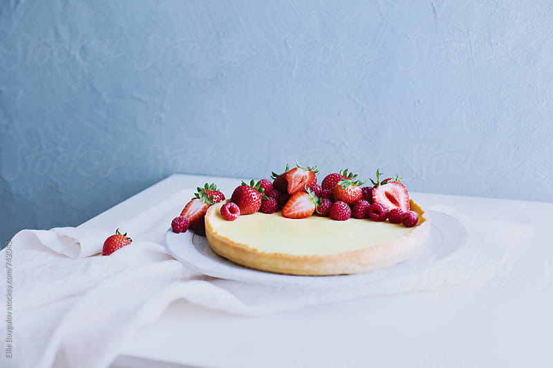 Lemon tart decorated with berries by Ellie Baygulov for Stocksy United
