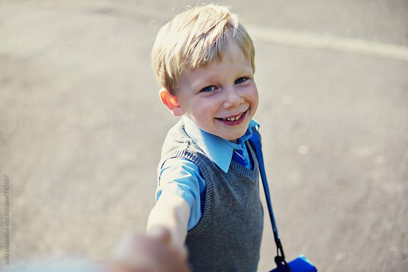 School boy walking to school  by sally anscombe for Stocksy United