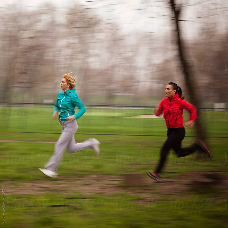 Two women jogging in the park on a rainy spring day.  by Mosuno for Stocksy United