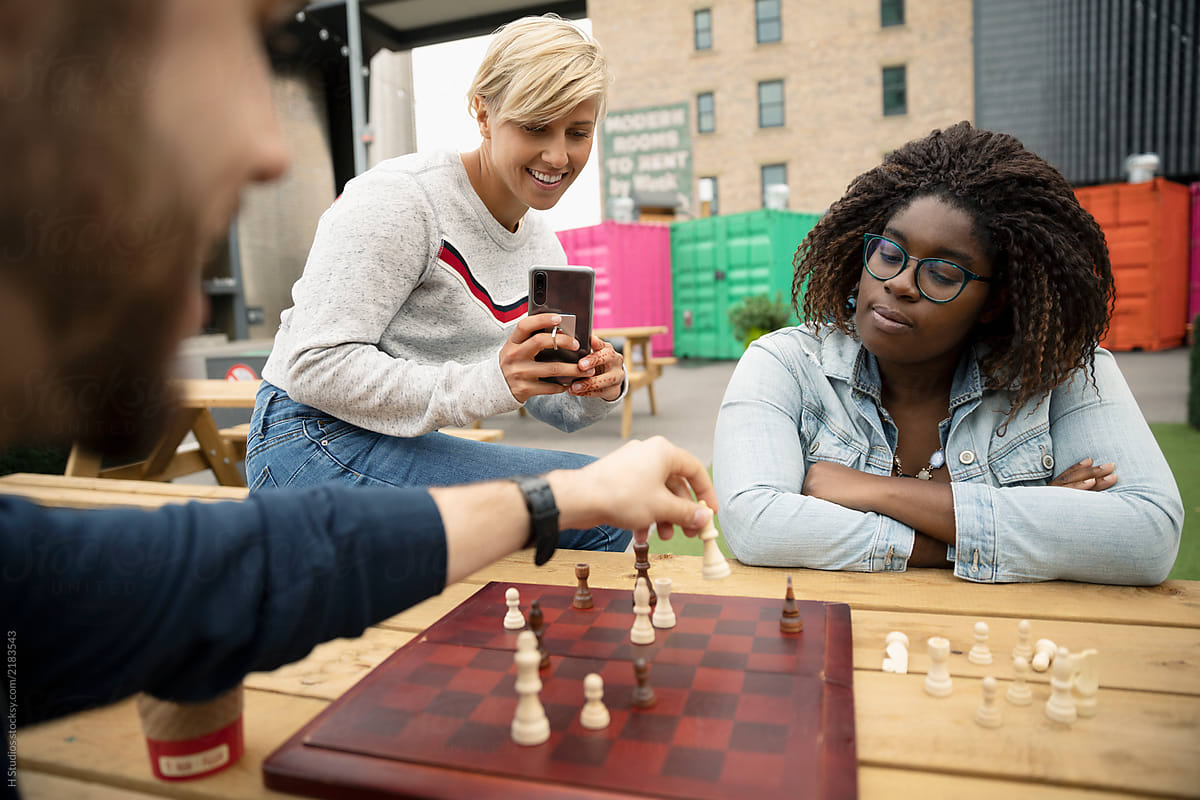 Stock Photo - Friends With Camera Phone Playing Chess At Urban Marketplace