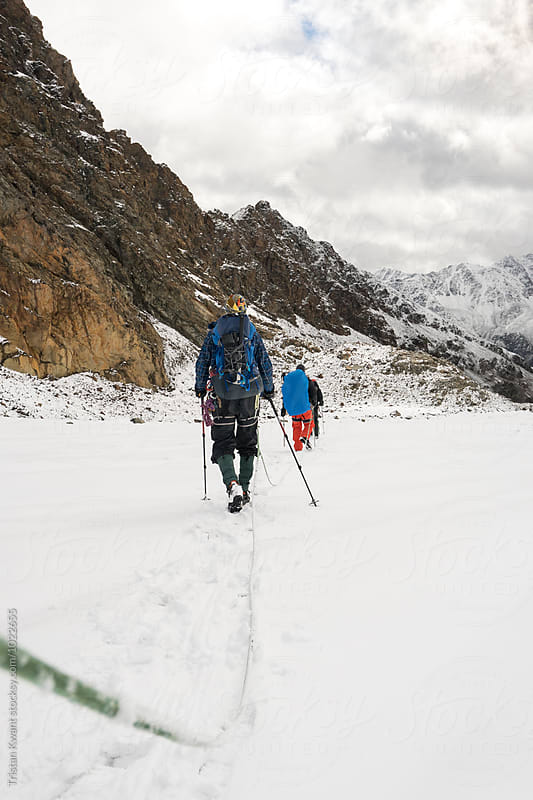 Two alpinists walking on a glacier in the alps. by Tristan Kwant for Stocksy United