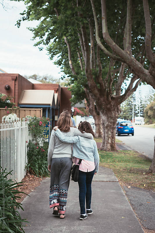 two girls walking along the street, hugging by Gillian Vann for Stocksy United