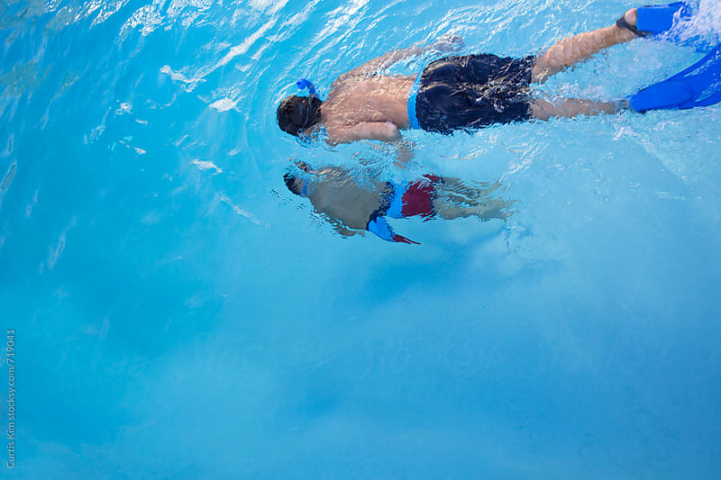 Boys snorkeling under water by Curtis Kim for Stocksy United