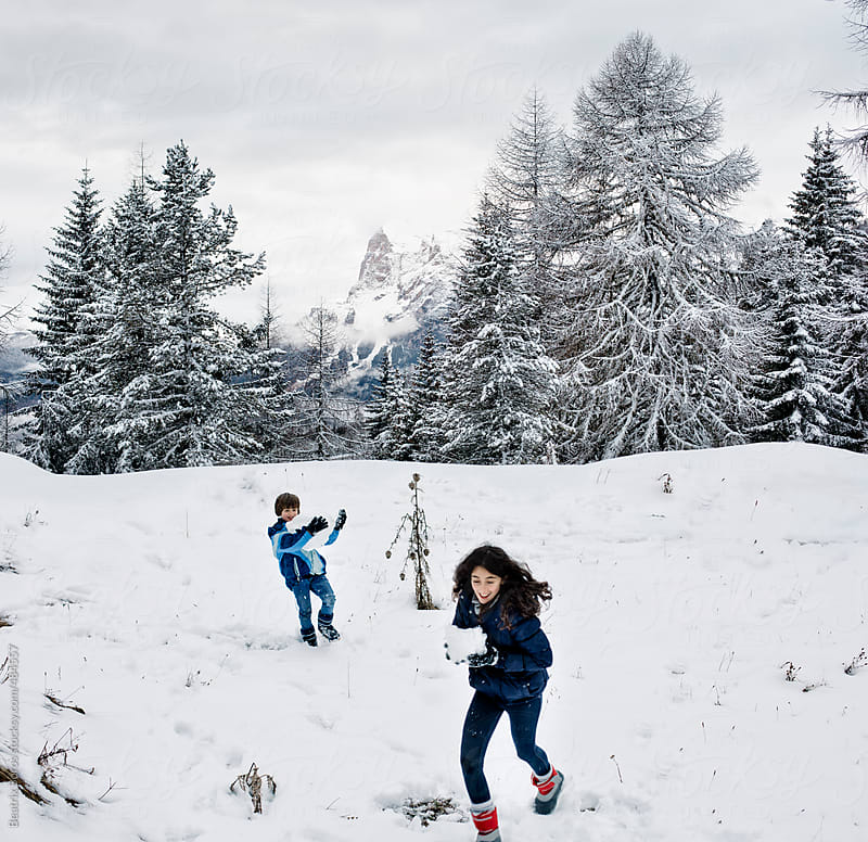 A girl and a boy playing in the snow in a beautiful mountan scenery by Beatrix Boros for Stocksy United
