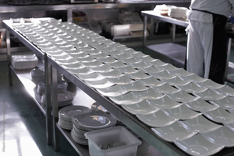 Table with rows of empty dishes waiting for food by Miquel Llonch for Stocksy United