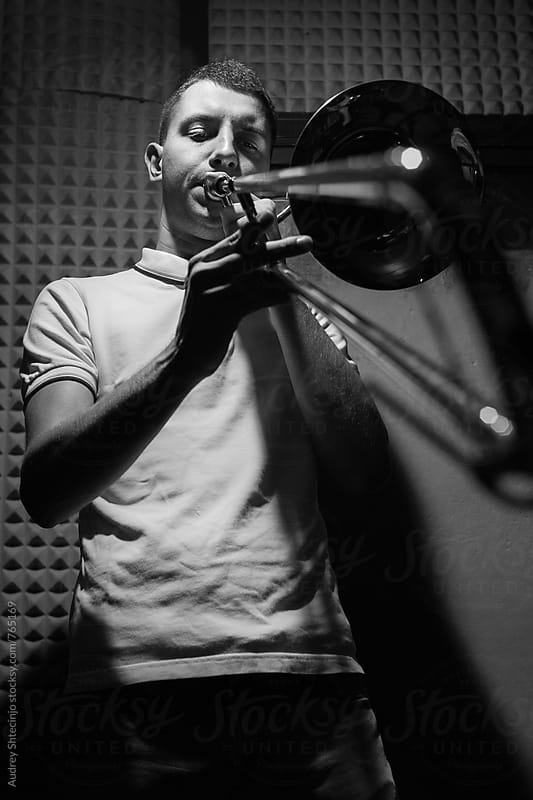 Ska/punk musician playing trombone on rehearsal om studio. by Audrey Shtecinjo for Stocksy United