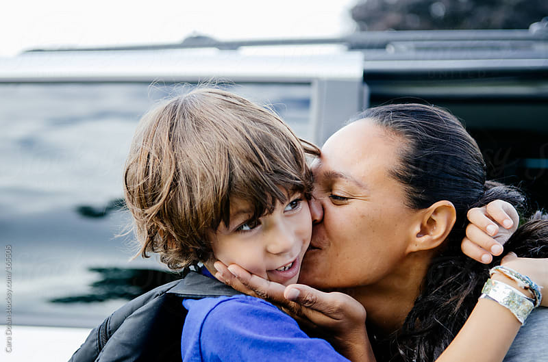 Mom kisses her son good bye as she drops him off at school by Cara Dolan for Stocksy United