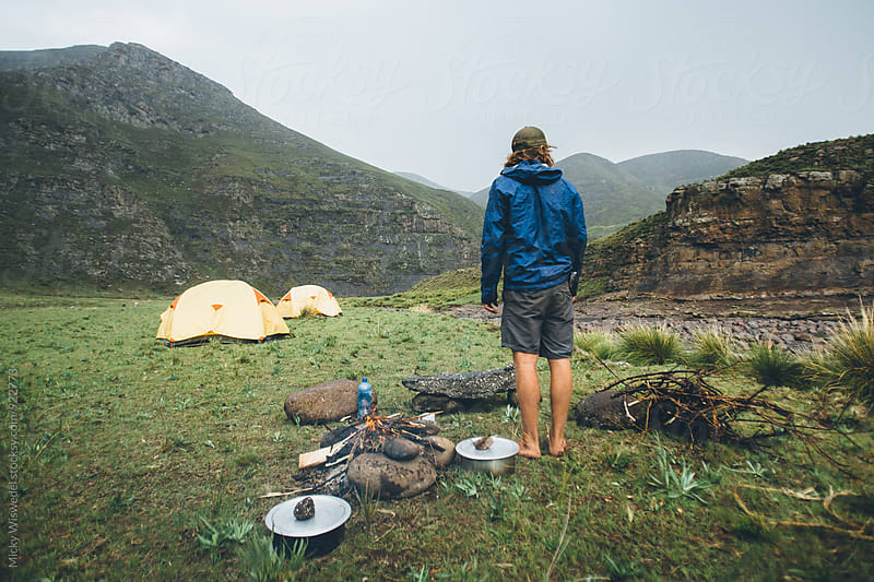 hiker outdoorsman standing by a campfire in camp on a rainy day in the mountains by Micky Wiswedel for Stocksy United