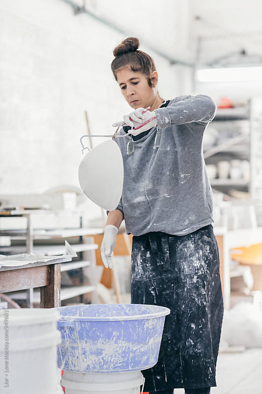 Female ceramic artist glazing a bowl in her studio by Lior + Lone for Stocksy United