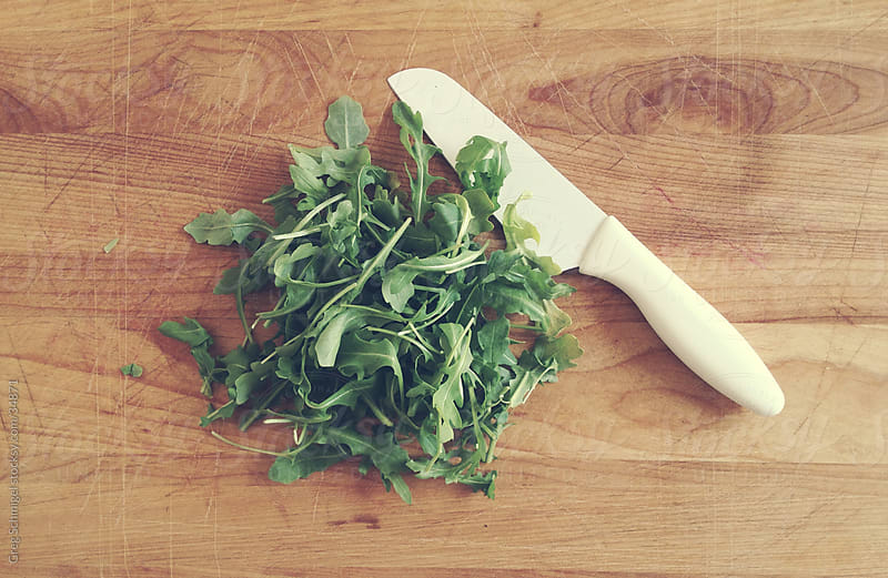 Chopped fresh arugula and knife by Greg Schmigel for Stocksy United