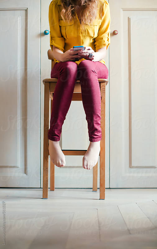 Woman With a Mobile Phone Sitting on a Chair by Lumina for Stocksy United