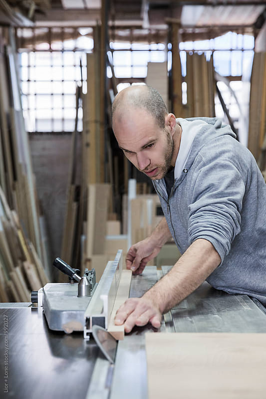 Closeup of a young carpenter slicing wood with a radial saw by Lior + Lone for Stocksy United