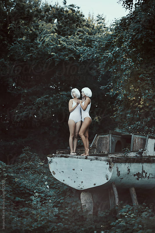 Two women standing on an abandoned boat by Jovana Rikalo for Stocksy United