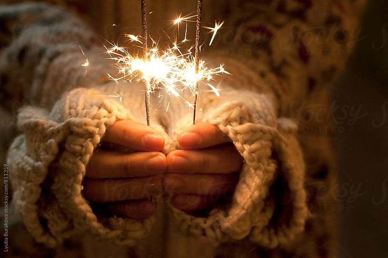 Close up shot of hands holding sparklers by Lyuba Burakova for Stocksy United