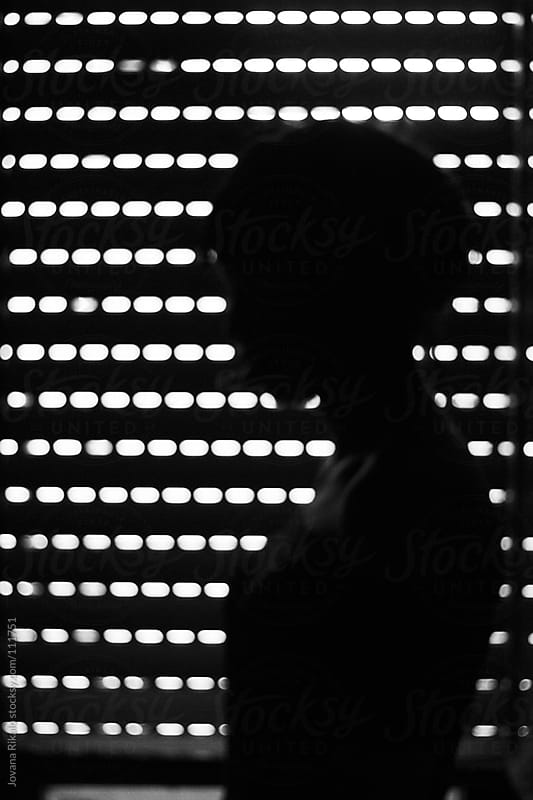 Silhouette of a girl in front of blinds by Jovana Rikalo for Stocksy United