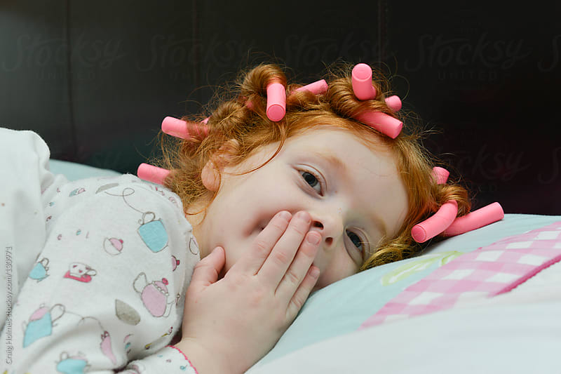 Little girl in bed wearing hair curlers by Craig Holmes for Stocksy United