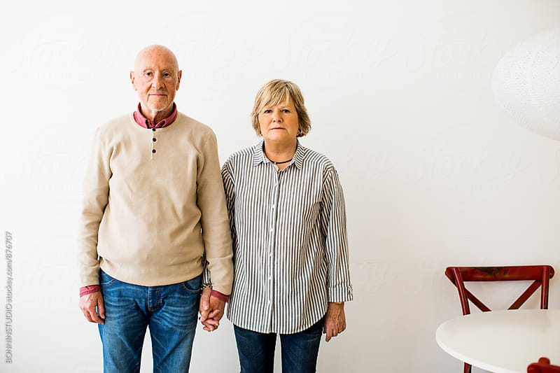 Portrait of an elderly couple standing on white. by BONNINSTUDIO for Stocksy United
