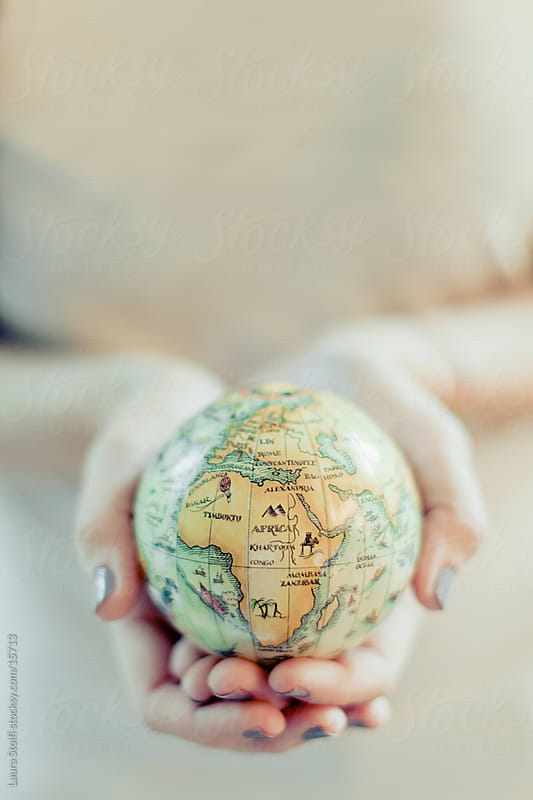 Girl holding in her hands a little globe in retro style by Laura Stolfi for Stocksy United
