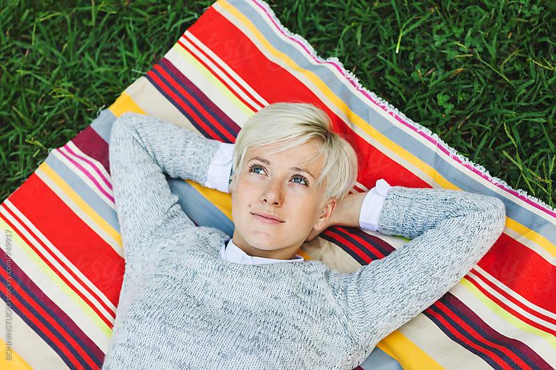 Blonde woman lying outside. by BONNINSTUDIO for Stocksy United