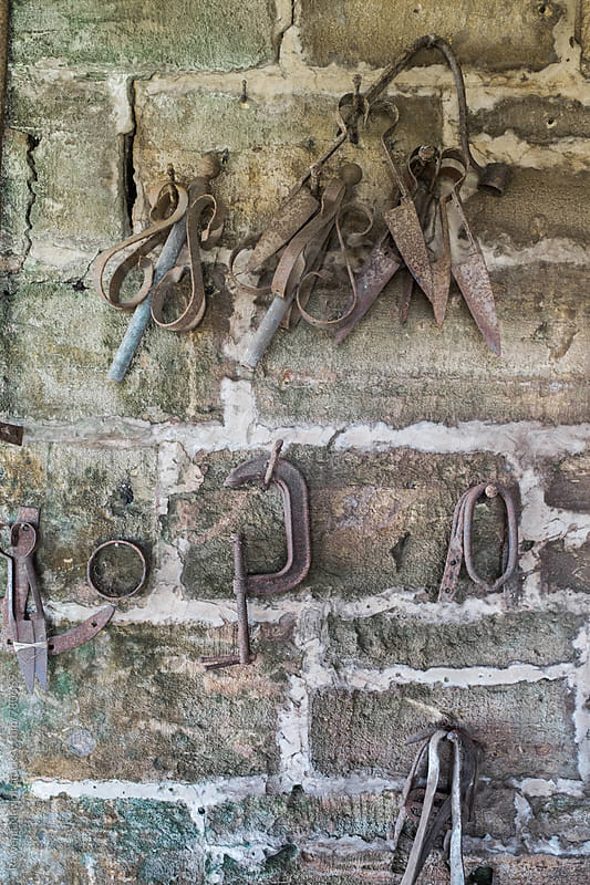 Collection of old iron tools hanging on barn wall by Rowena Naylor for Stocksy United