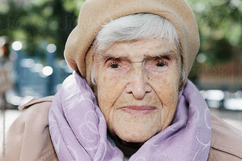 Portrait of a stern elderly woman in her 90s sitting outside in the park by Mihael Blikshteyn for Stocksy United