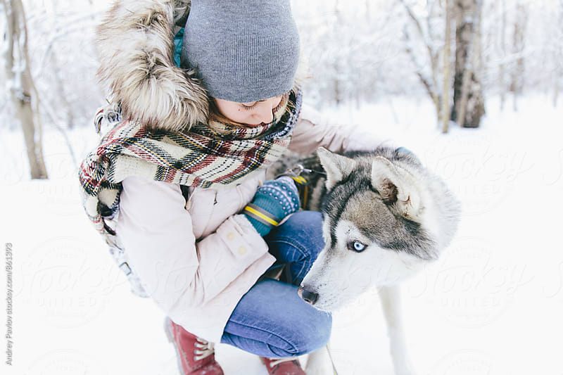 Close-up of woman and husky in snowy forest by Andrey Pavlov for Stocksy United