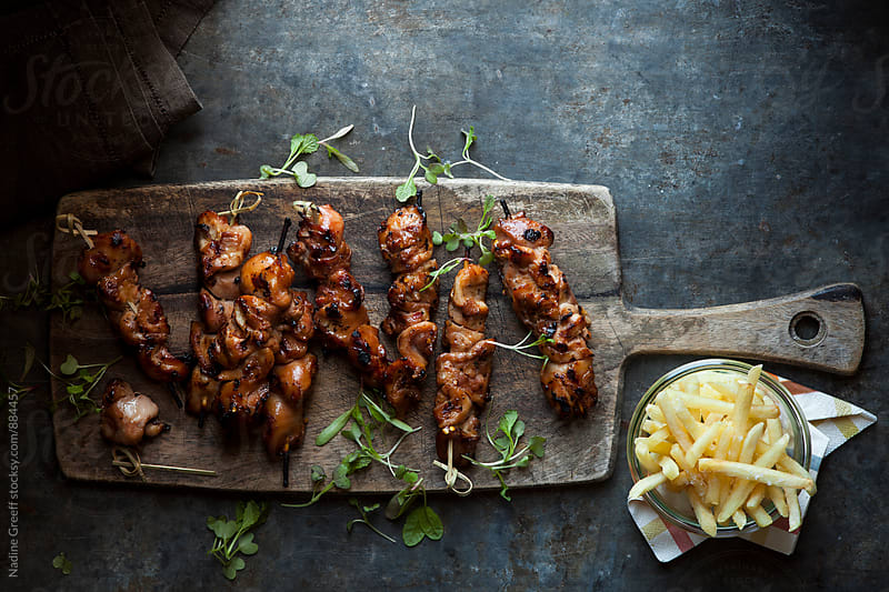 Chicken kebab with a side of potato fries by Nadine Greeff for Stocksy United