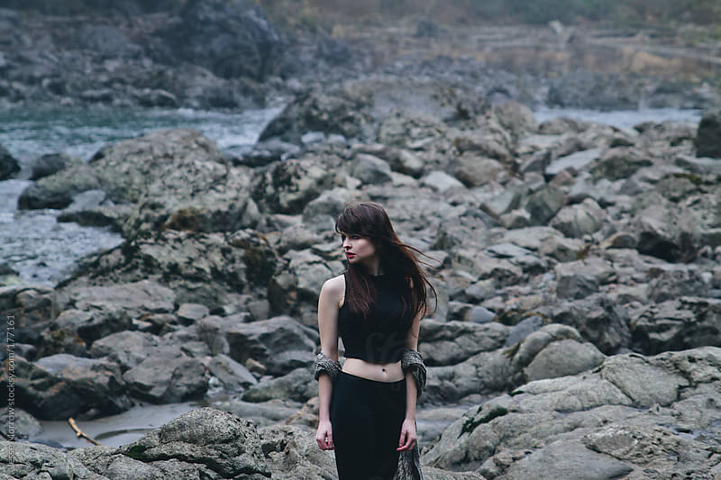 Young woman in front of water by Jesse Morrow for Stocksy United