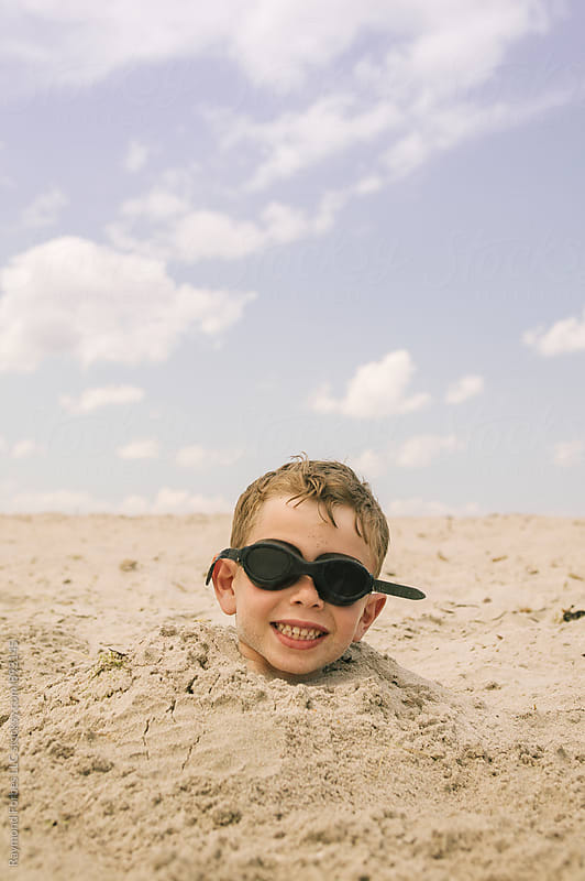 Boy Buried in Sand Cape Cod, Massachusetts by Raymond Forbes LLC for Stocksy United