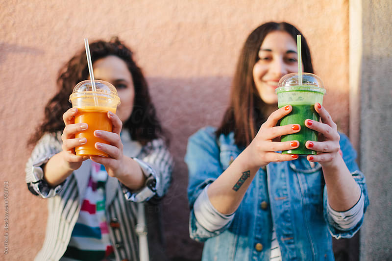Two female friends drinking smoothies outdoors by VeaVea for Stocksy United