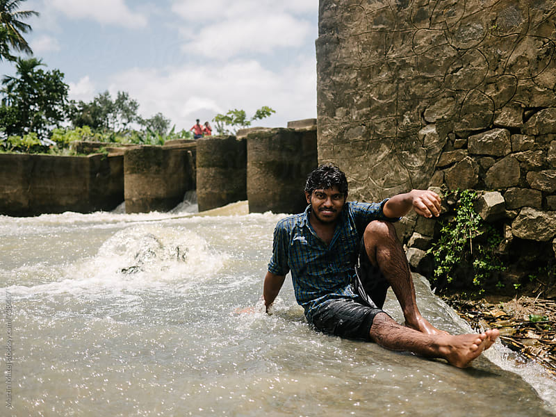 Indian boy sitting in the river by Martin Matej for Stocksy United