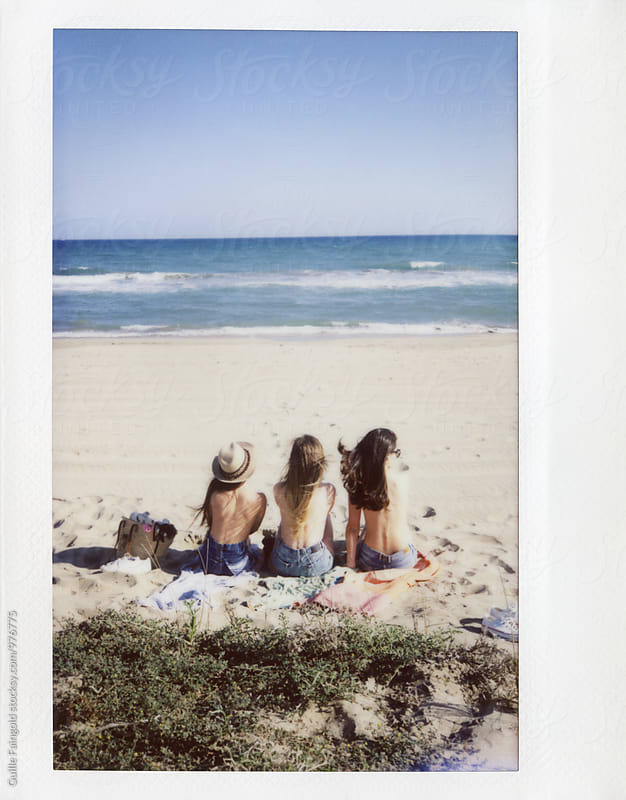 Three girlfriends sitting on beach by Guille Faingold for Stocksy United