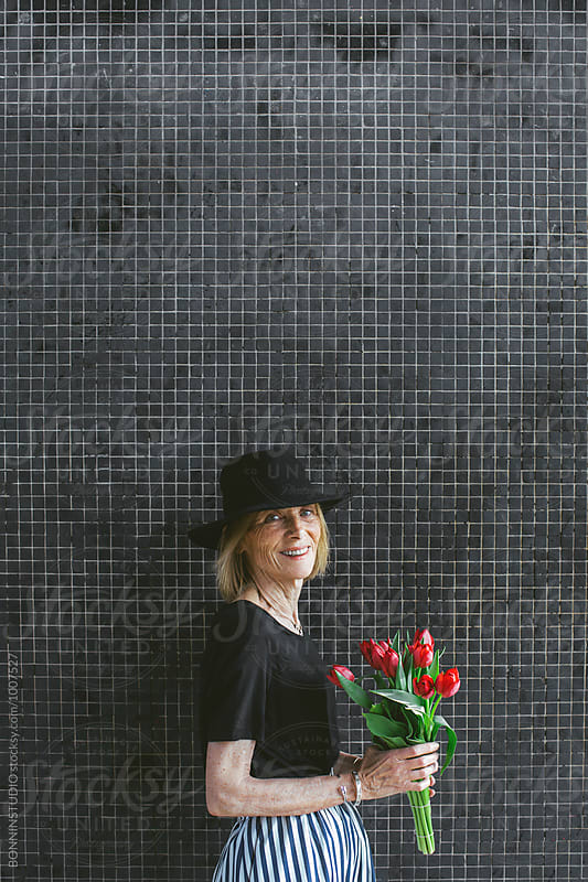 Portrait of a stylish senior woman holding a bouquet of red tulips.  by BONNINSTUDIO for Stocksy United