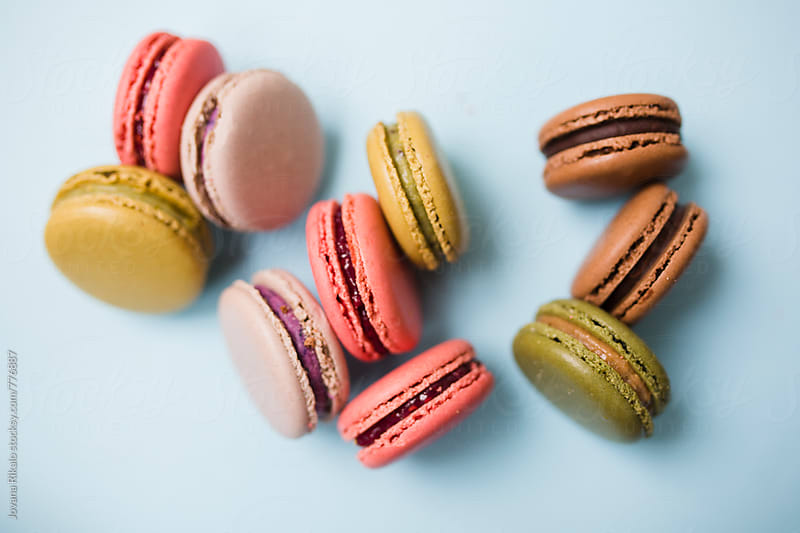 Colorful macaroons on a blue background by Jovana Rikalo for Stocksy United