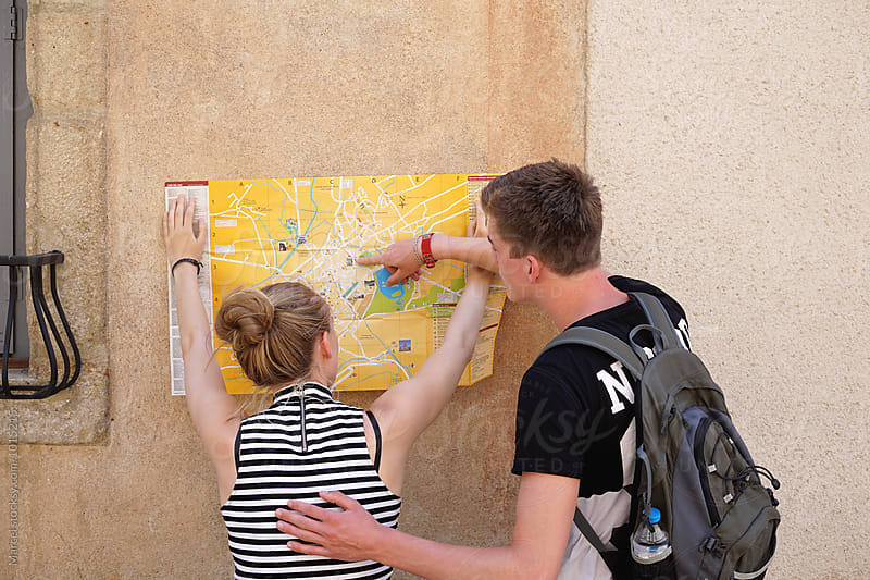 Young couple looking at a map by Marcel for Stocksy United