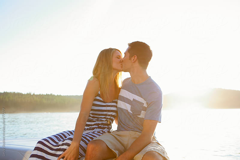 Happy couple kissing on lake at sunset by Linzy Slusher for Stocksy United